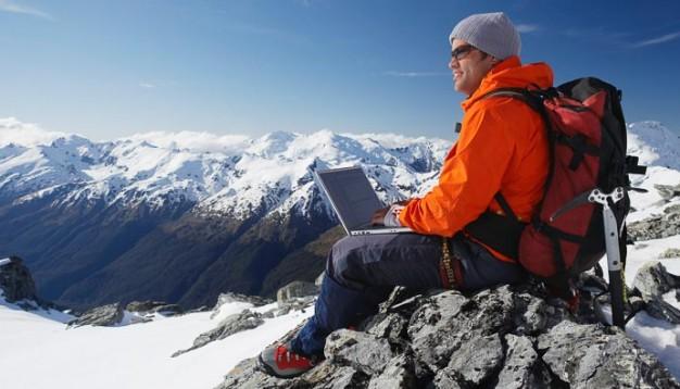 Man on laptop on top of snowy mountain