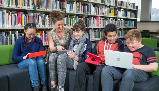 Māori teacher sits with 4 students in the library