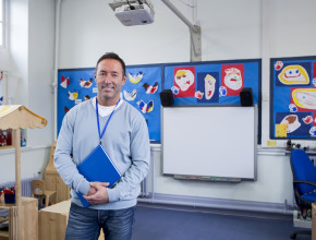 A male teacher stands in front of a whiteboard and children's art in a classroom. He carries a clipboard and is smiling.