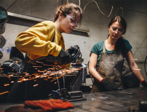 Two female apprentices learning how to cut metal in a workshop