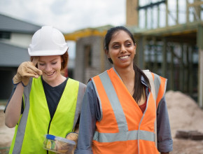 Two smiling construction workers who are women