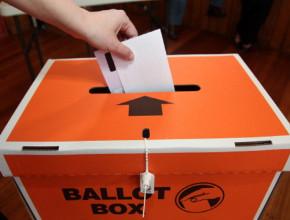 A hand places a voting ballot in an orange ballot box