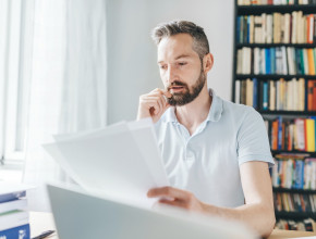 A man sits at a home desk reading sheets of paper