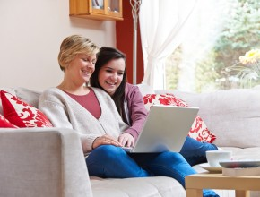 Mother and daughter look at a laptop together