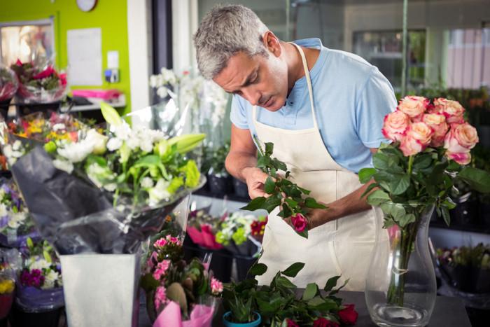 A male florist arranging roses into a bouquet