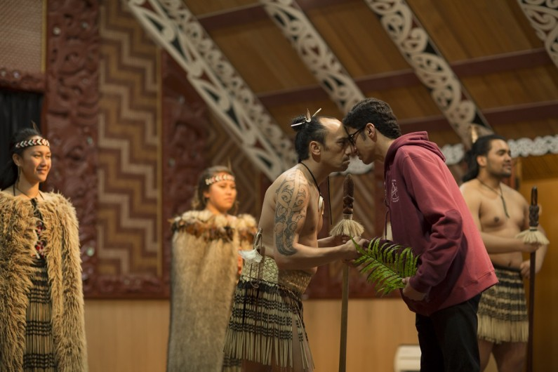 In the meeting house of a marae a man hongi with a young man.