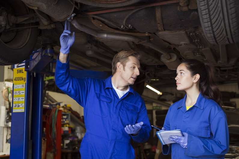 Apprentice mechanic holding a notepad looks at her trainer as he points to the muffler system of a car on a hoist above them.