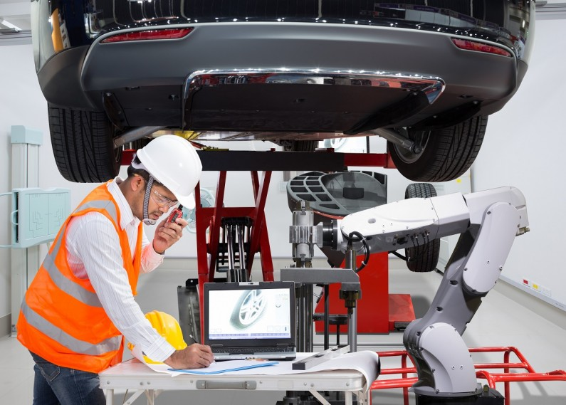 Automotive electrician works on a car alongside a robot