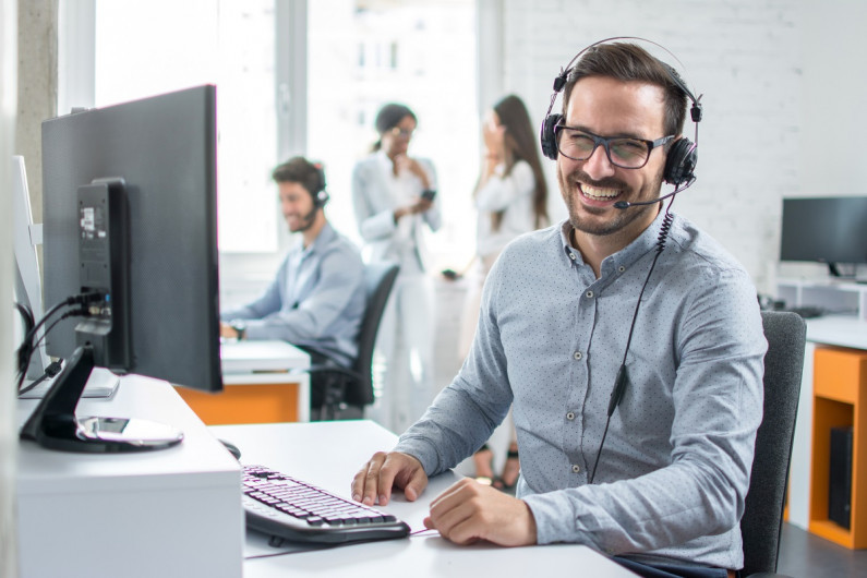 Man in call centre smiles at the camera