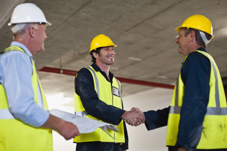 Three men in hard hats greet each other.