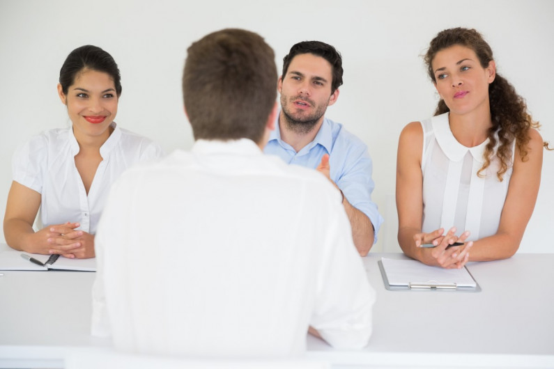 Two women and a man sitting at a table interviewing a man opposite them