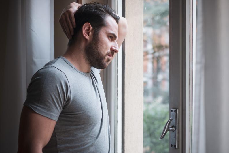 A man looks out an open door