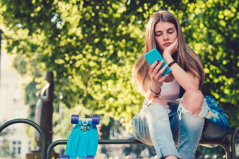 A teenage girl looks concerned as she looks into a mobile phone. She is sitting on a park bench under a tree with a skateboard beside her. The colours are green, light blue, turquoise.