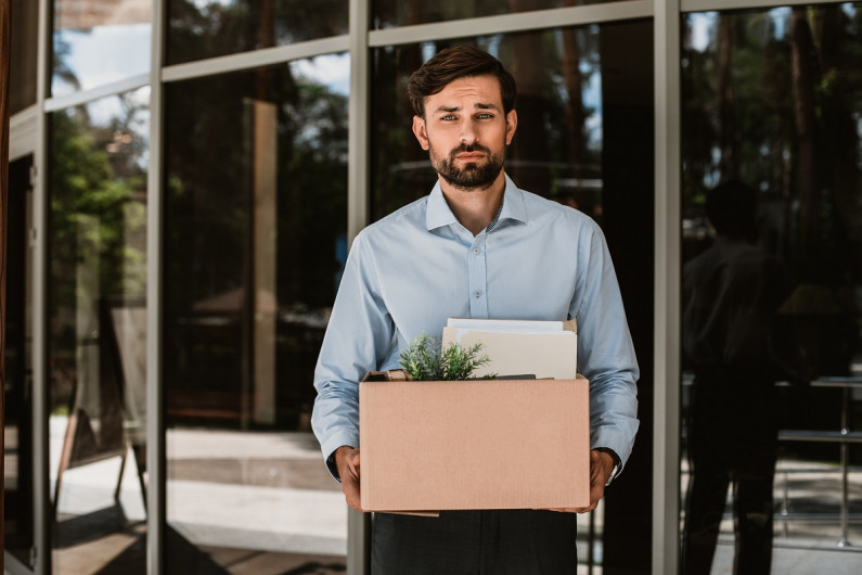 Man leaving office carrying plants and files in a box