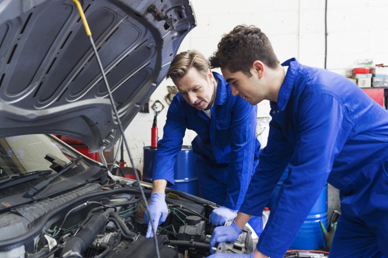 Apprentice and mechanic looking under a car's bonnet