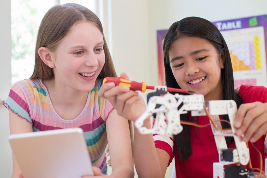 Two teenage girls building a robot