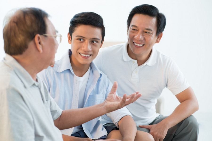 A teenage boy sits between his grandad and father as they chat
