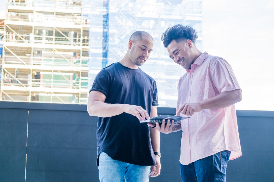 Two men look at a tablet as they stand outside some scaffolding.