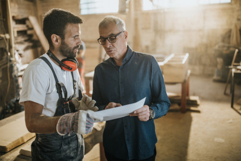 Two men in a workshop discuss plans