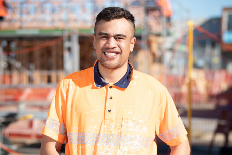 Young man on building site is wearing safety gear and smiling at the camera.