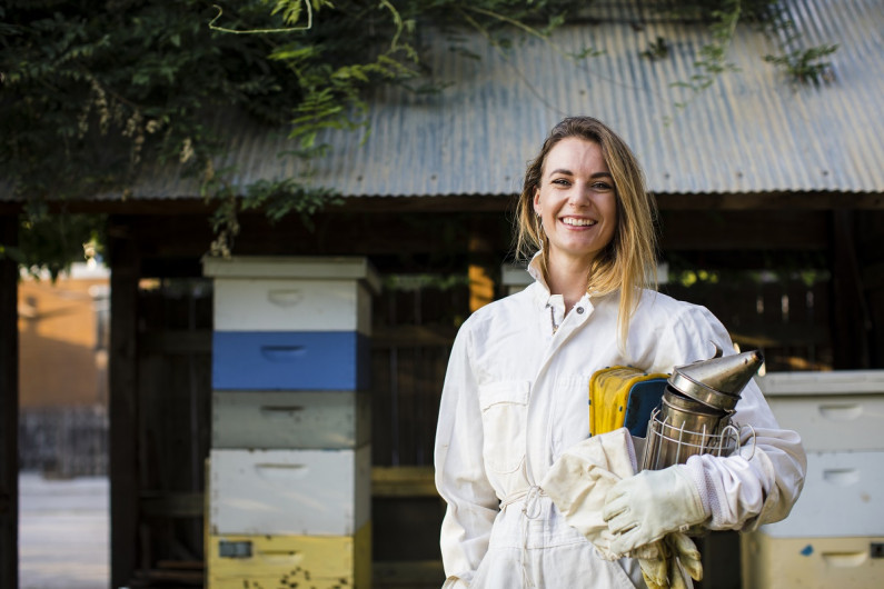 Woman beekeeper in work clothes standing outside an apiary