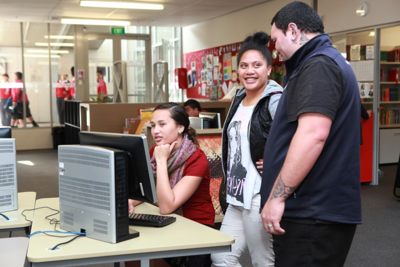 A teacher talks to two students at a computer desk in a library