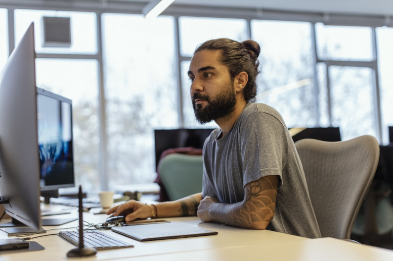 Young man in an office or library searches online for jobs