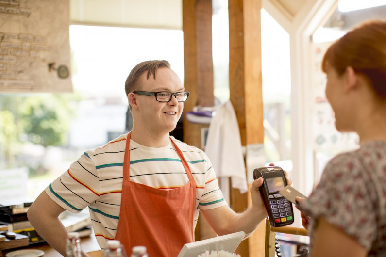 Man wearing apron in a cafe holds up EFTPOS machine while a woman swipes her card.