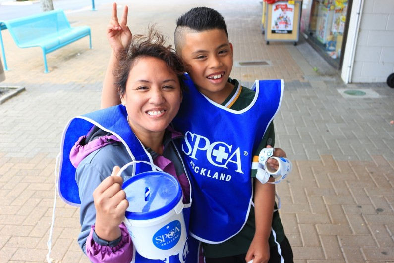 A mother and child hold a bucket on the street as they collect for the SPCA