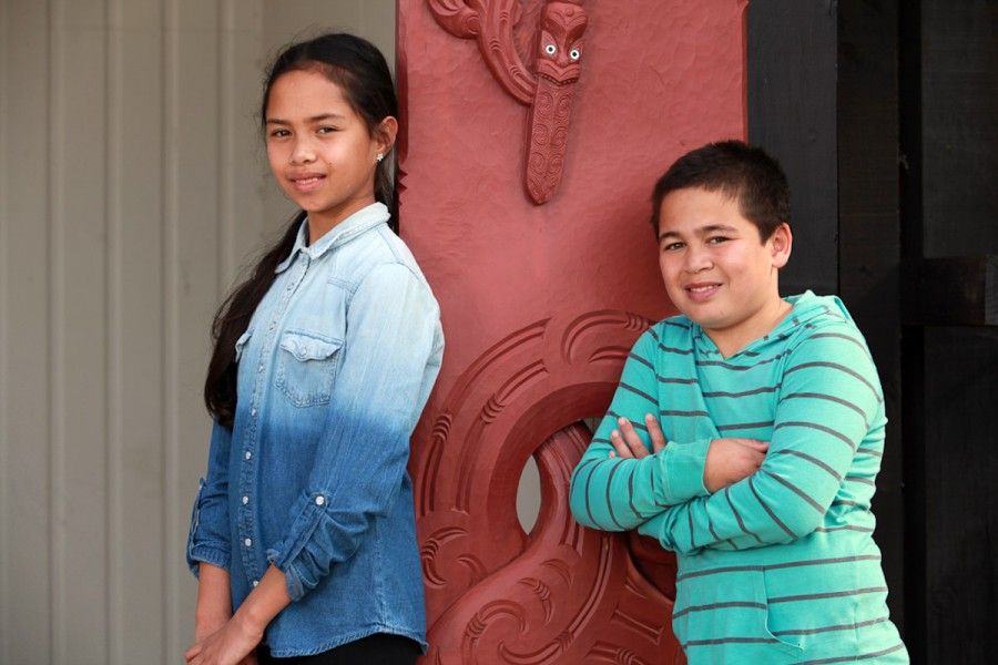 Two Maori children stand by a carved entrance