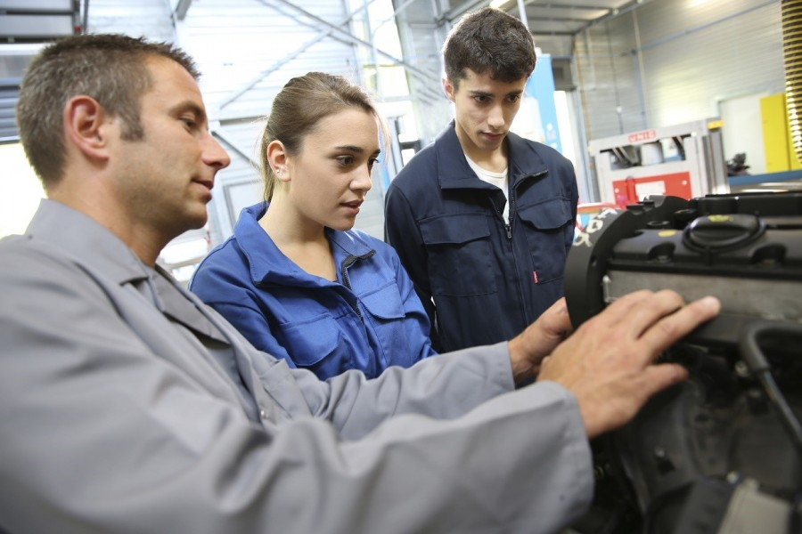 A male automotive engineer shows tow students how to use machinery in a workshop.