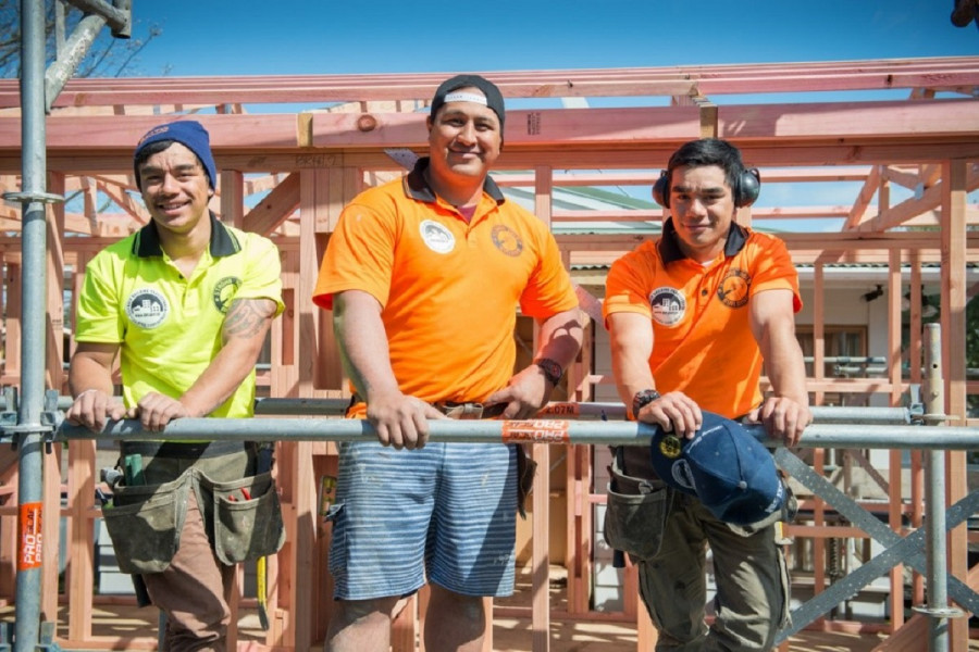 Three male construction workers stand on scaffolding and smile at the camera