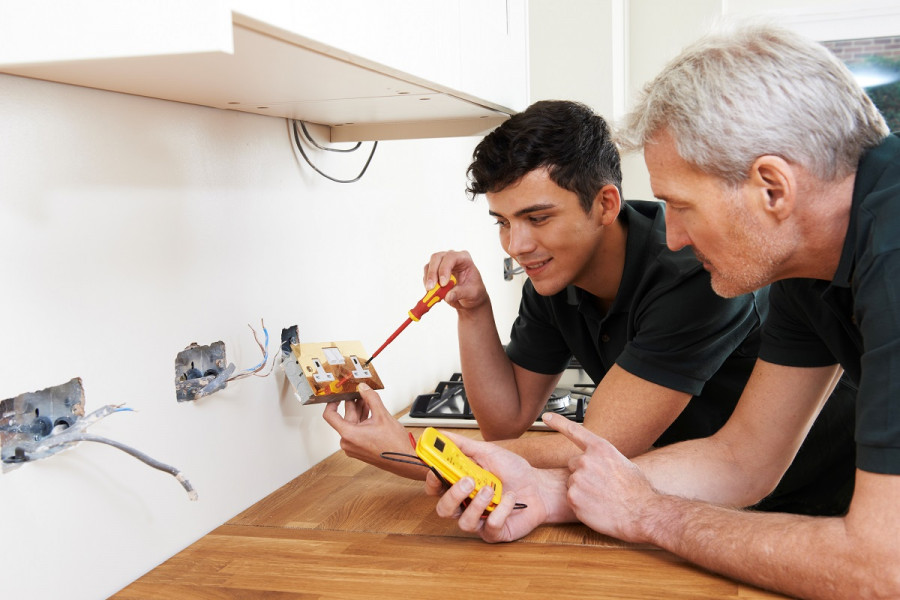 An electrician and an apprentice are lying on the floor while the apprentice opens up an electrical plug