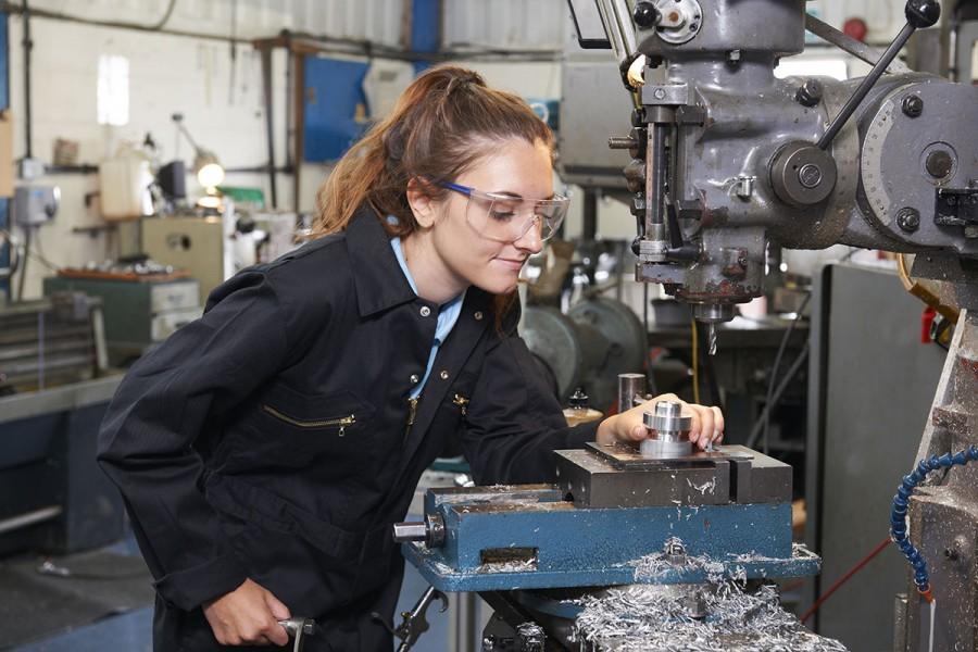A young apprentice operates a drill