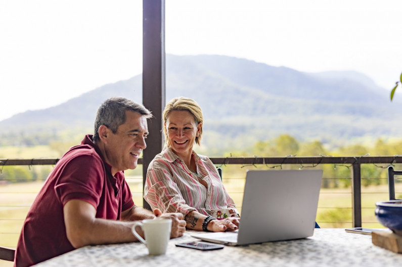 A man and women sit at a kitchen table and laugh about something. A laptop sits in front of them and outside you can see a hill.