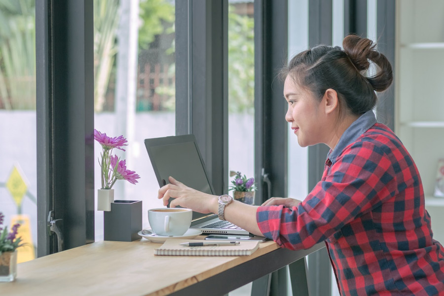 Young woman sits in cafe near the window and looks for jobs on her laptop