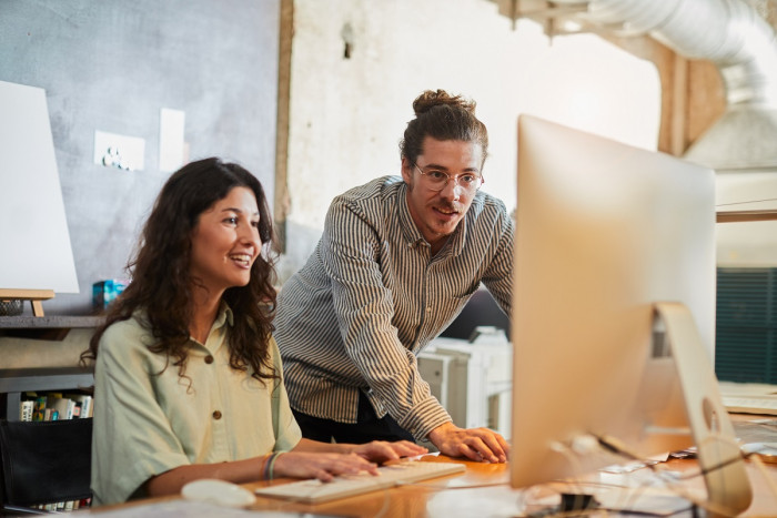 Two advertising specialists look at work on a computer