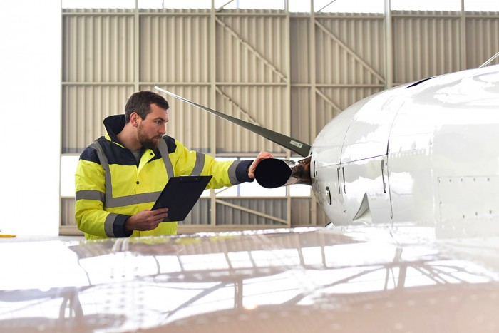 Aeronautical engineer inspects an aeroplane in an airport hangar