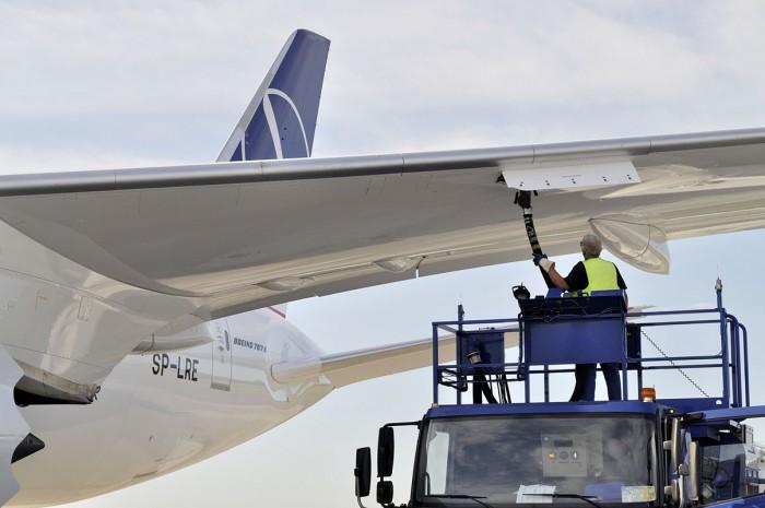 An aircraft refueller in a vehicle refuels an aeroplane on the tarmac