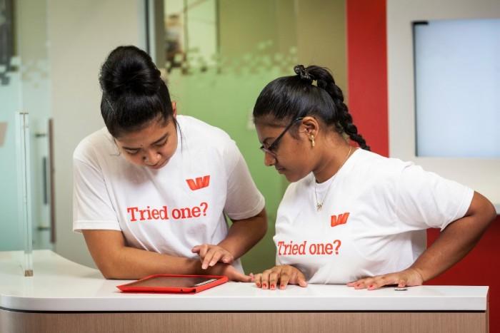 Two interns checking an ipad at a bank