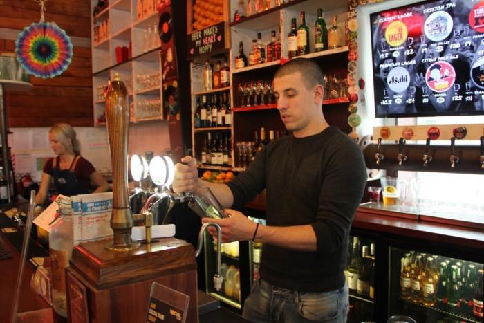 Steve Clay serves drinks behind a bar