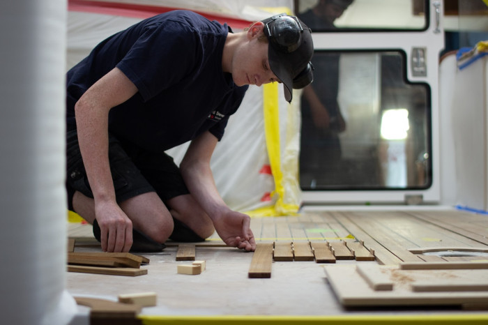 A man kneels on a floor inside a new boat, linking up wooden decking planks