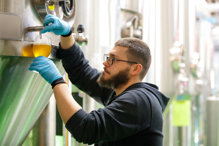 A brewer testing his brew during fermentation