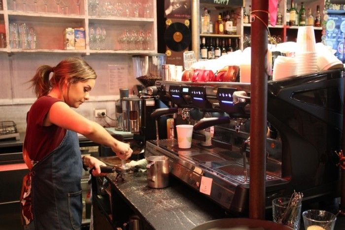 A barista prepares coffee grinds for a cup of coffee