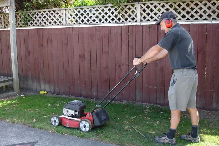 Rex Baker mowing grass next to a fence