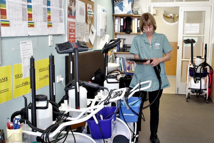 Julie Pope checks the attachment to a steam cleaner in a hospital office. Other steam cleaners are also pictured