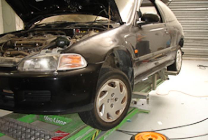 A black car in a panelbeating workshop awaiting work