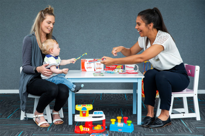 Community karitāne and parent holding child sitting at a table talking about oral health