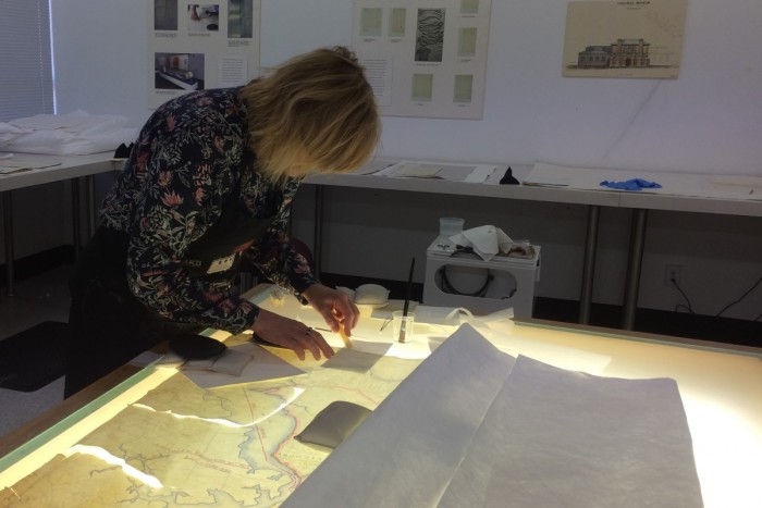 Anna Whitehead stands over a light table fixing a badly damaged map