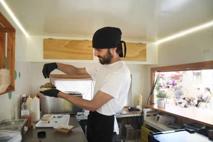 A cook prepares a burger in a food truck